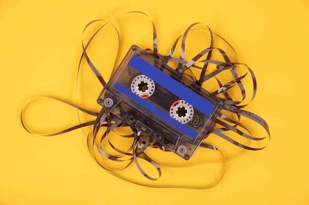 Stara kaseta magnetofonowa z rozwiniętą taśmą na żółtym tle.
