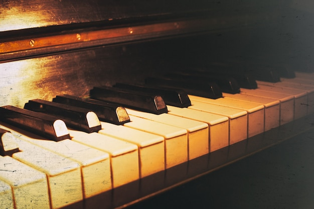 Stara klawiatura fortepianu z bliska jako tło muzyczne. z zadrapaniami i kurzem teksturą papieru