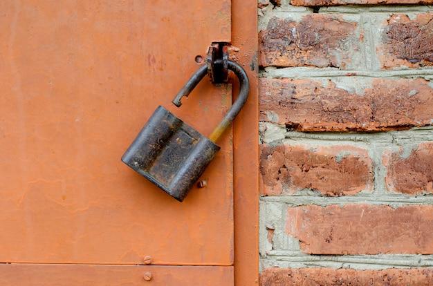 Stara kłódka na metalu drzwi. czerwony ściana z cegieł