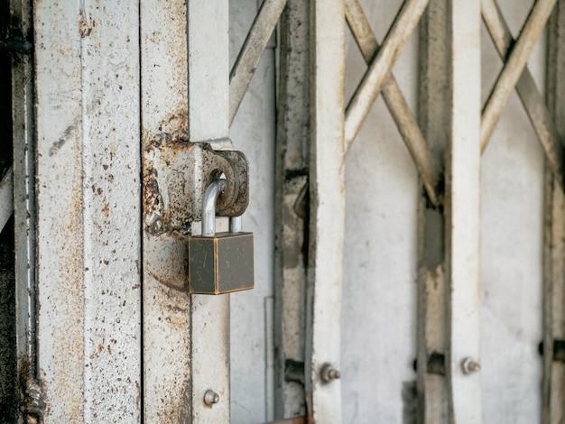 Stara kłódka na zardzewiałych żelaznych drzwiach przesuwnych. zamknij się z miejscem na tekst.