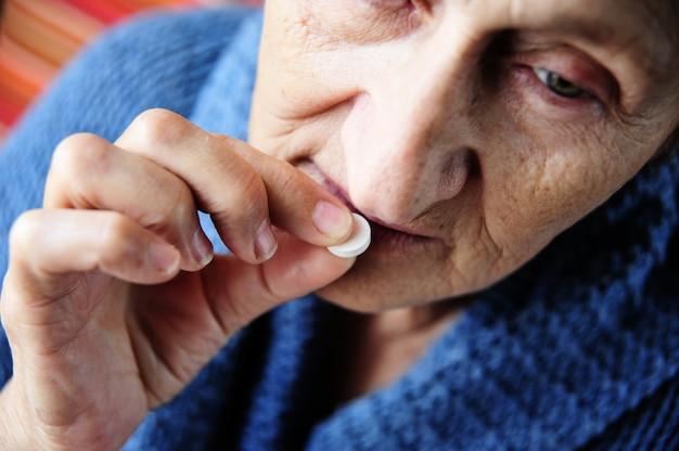 Stara kobieta bierze pigułkę