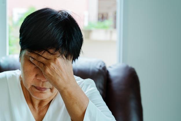 Stara kobieta cierpi na ból głowy, stres, migrenę, pojęcie problemu zdrowotnego