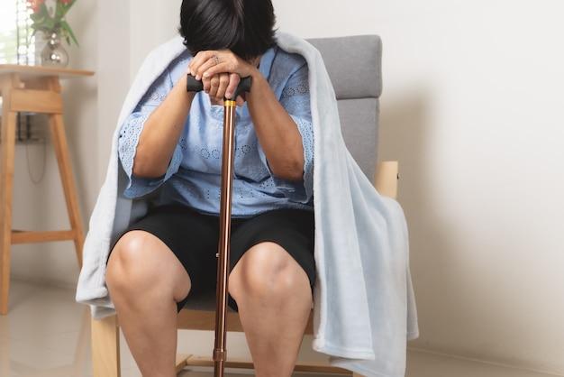 Stara kobieta cierpi na bóle głowy, stres, migrenę, pojęcie problemu zdrowotnego
