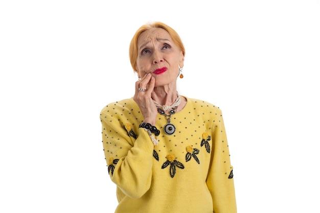 Stara kobieta cierpiąca na ból zęba zdenerwowana pani patrząca na odizolowany ból spowodowany chorobą dziąseł