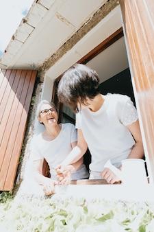 Stara Kobieta I Jego Córka Bawią Się W Oknach Podczas Super Słonecznego Dnia, Uśmiechając Się Szczęśliwa Koncepcja Emerytury, Dzień Matki, Rośliny I Relaks Premium Zdjęcia