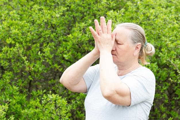 Stara kobieta medytuje trzymając ręce blisko głowy.