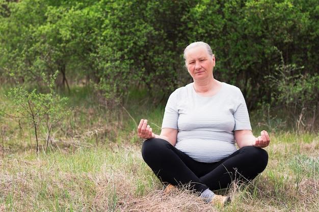 Stara kobieta medytuje w pozycji lotosu.