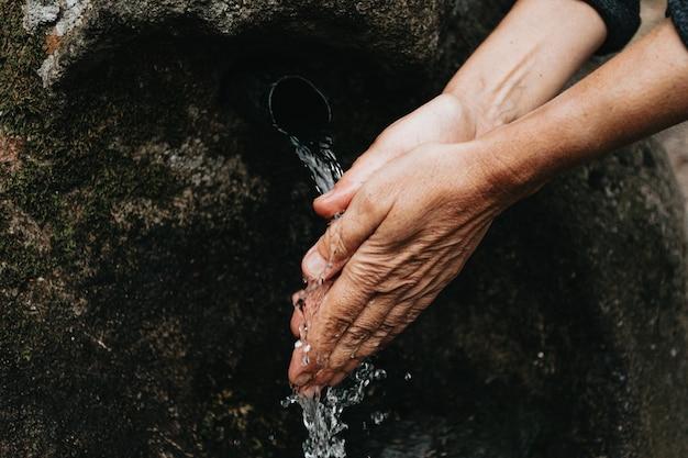 Stara kobieta mycie rąk z bliska w fontannie źródłowej z naturalną wodą