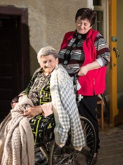 Stara kobieta na wózku inwalidzkim i jej córka w pobliżu domu