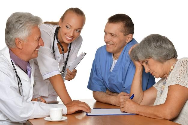 Stara kobieta odwiedza lekarzy na białym tle
