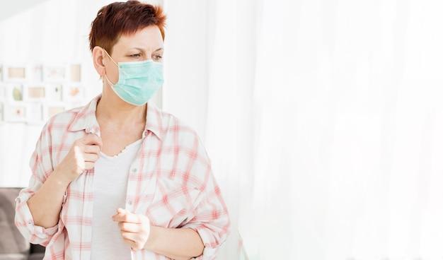 Stara kobieta patrzeje przez okno w domu z medyczną maską