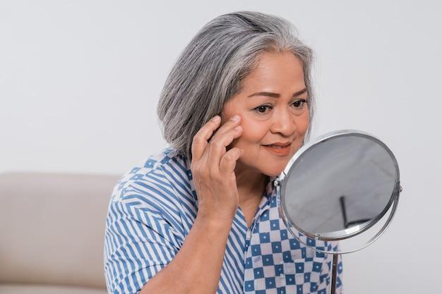 Stara kobieta patrzy w lustro