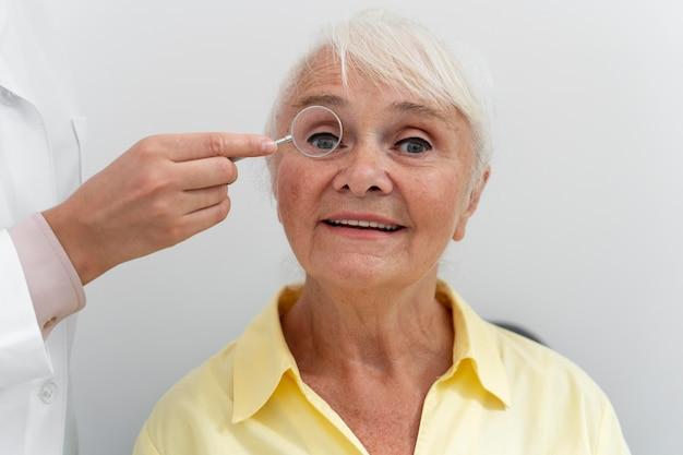 Stara kobieta poddawana badaniu wzroku w klinice okulistycznej