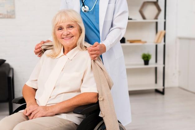 Stara kobieta pozuje w wózku inwalidzkim