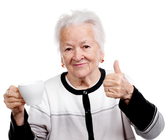 Stara kobieta przy filiżance kawy lub herbaty i pokazuje tak znak na białym tle