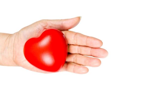 Stara kobieta ręka trzyma czerwone serce w oddawaniu pomocy, aby dać miłości ciepło. światowy dzień zdrowia.