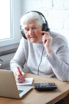 Stara kobieta siedzi przy stole przed laptopem ze słuchawkami i pisze do notatnika.