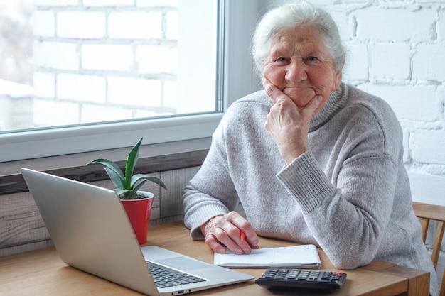 Stara kobieta siedzi przy stole przed laptopem.