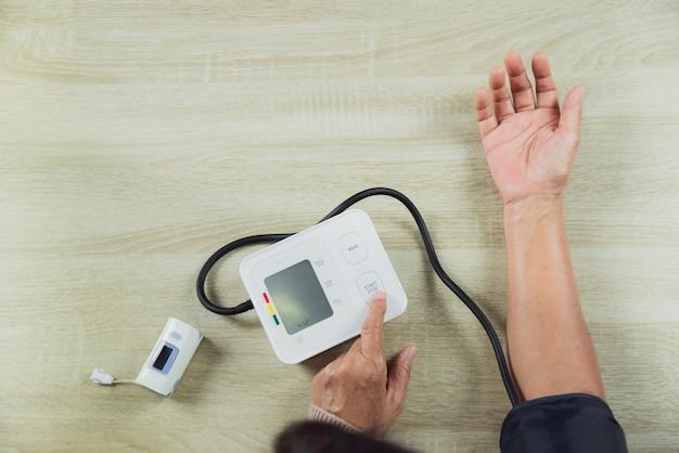 Stara kobieta sprawdza ciśnienie krwi poziom na stole z ciśnieniomierzem