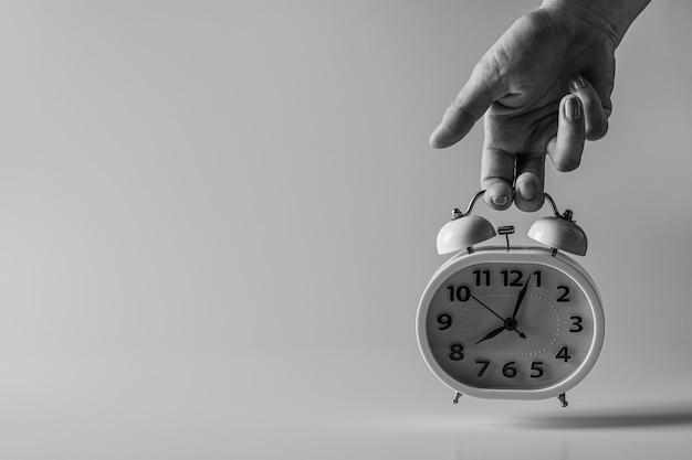 Stara kobieta trzyma budzik w dłoni. myślenie i kontrola pomysłów na czas.