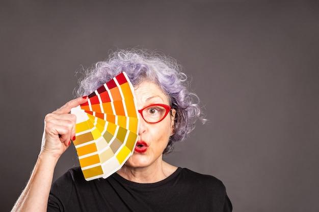 Stara kobieta trzyma paletę kolorów na szarej przestrzeni