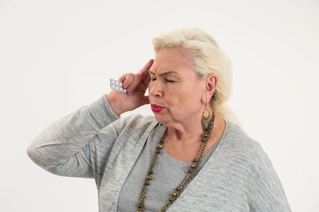 Stara kobieta trzyma pigułki odizolowana starsza pani ma ból głowy