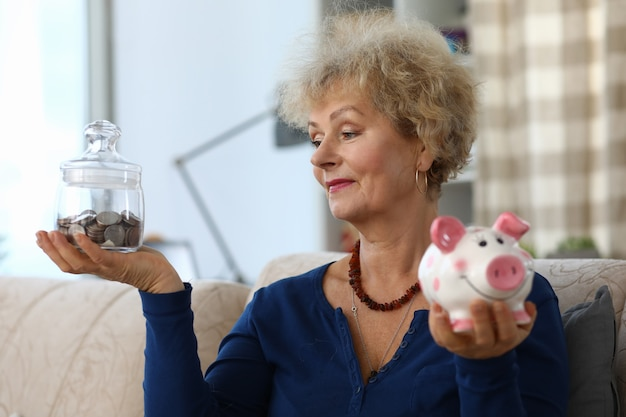 Stara kobieta trzyma skarbonkę z oszczędnościami w dłoniach.