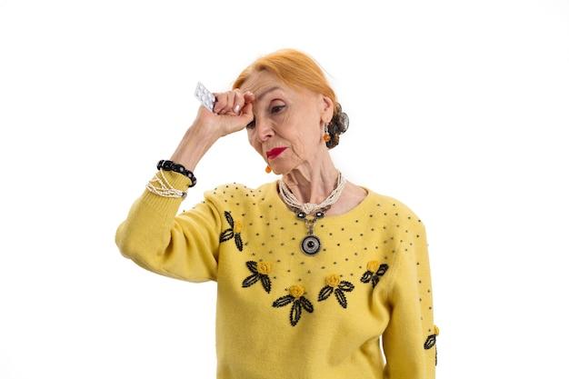 Stara kobieta trzymająca lekarstwo smutna starsza pani na białym tle potrzebuję aspiryny