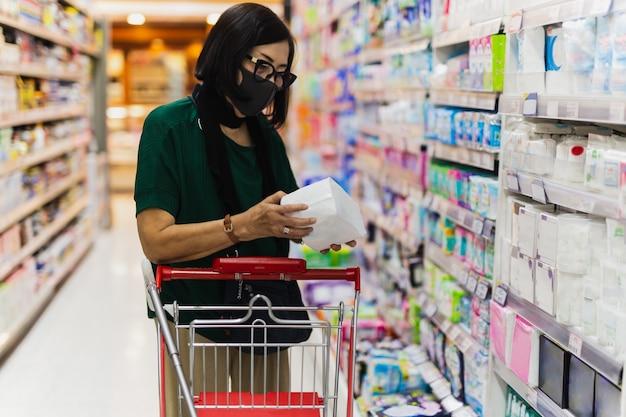 Stara kobieta ubrana w maskę ochronną w sklepie spożywczym podczas covid-19.