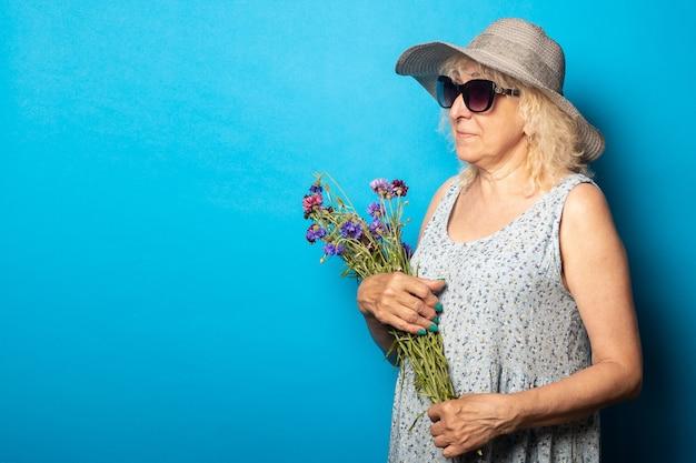 Stara kobieta w kapeluszu i sukience z szerokim rondem trzyma bukiet kwiatów i spogląda w bok na niebieską ścianę.