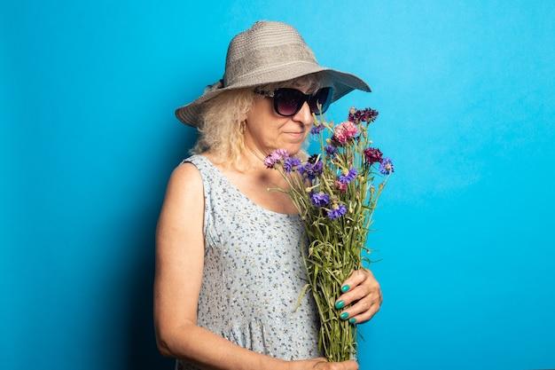 Stara kobieta w kapeluszu i sukience z szerokim rondem wącha bukiet kwiatów na niebieskiej ścianie.