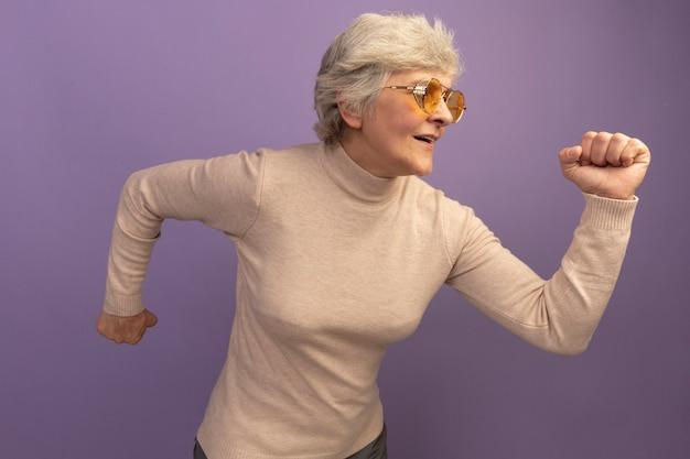 Stara kobieta w kremowym swetrze z golfem i okularach przeciwsłonecznych, zaciskająca pięści, patrząca prosto podczas biegu