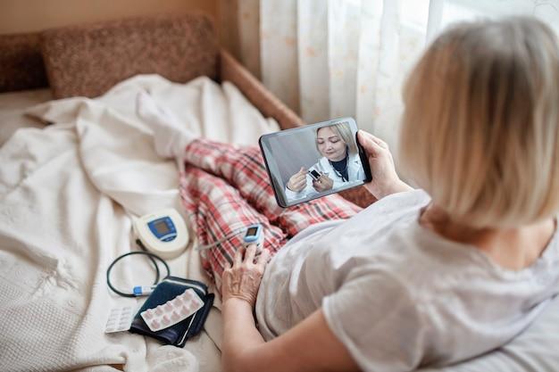 Stara kobieta w łóżku patrząc na ekran laptopa i konsultując się z lekarzem online w domu, telezdrowie