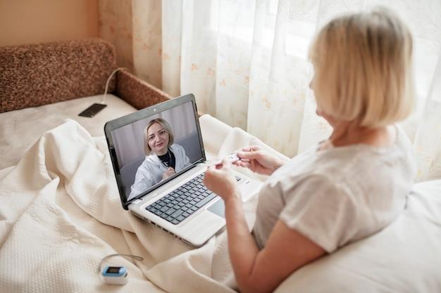 Stara kobieta w łóżku patrzy na ekran laptopa i konsultuje się z lekarzem online w domu, usługi telezdrowia podczas blokady, zdalna rozmowa wideo, aplikacja nowoczesnej opieki zdrowotnej