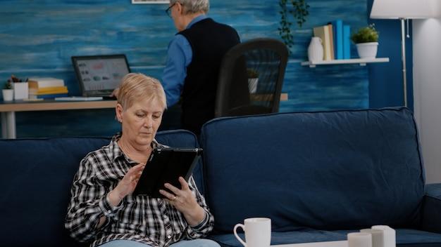 Stara kobieta w średnim wieku relaksujący trzymający tablet czytający e-książkę, siedzący na kanapie w domu, podczas gdy starszy dorosły mężczyzna pracuje na laptopie w tle. osoba korzystająca z notatnika przeglądającego zakupy w internecie