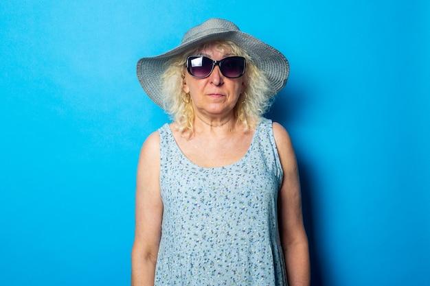 Stara kobieta w sukni i kapeluszu z okularami przeciwsłonecznymi