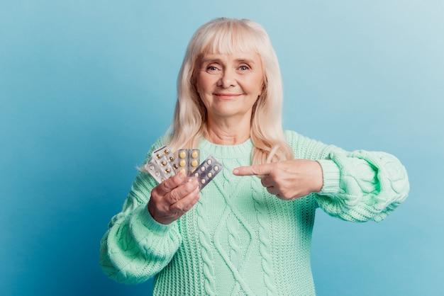 Stara kobieta wskazujący palec produkt medyczny trzymaj tabletki w ręku na niebieskim tle