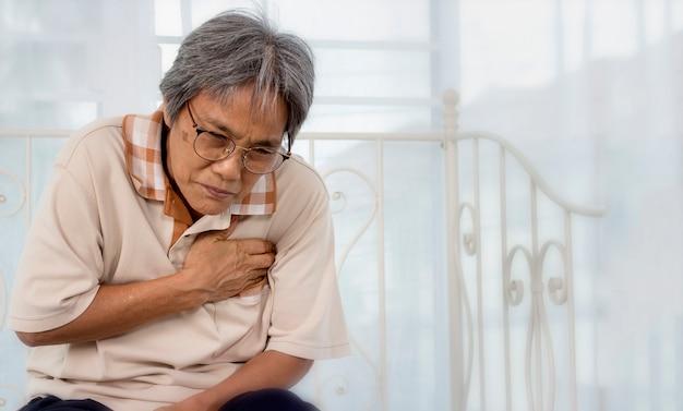 Stara kobieta z bólem w klatce piersiowej cierpiącym na zawał serca w domu.