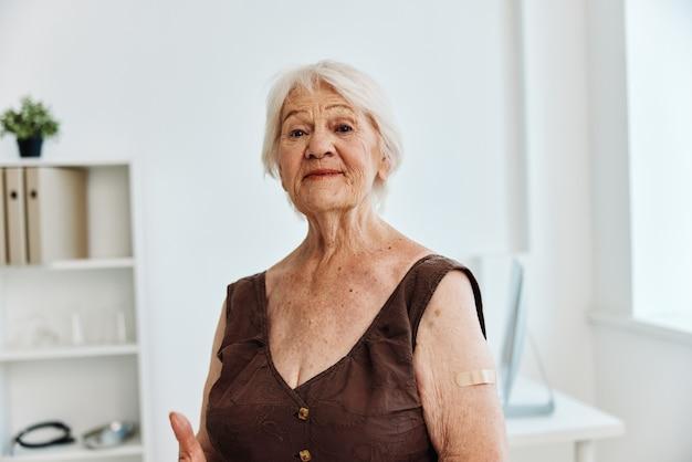 Stara kobieta z gipsem na ramieniu paszport szczepionkowy covid