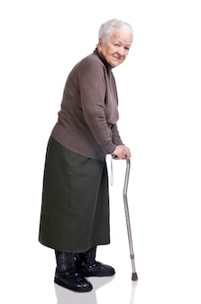 Stara kobieta z laską pozowanie studio na białym tle