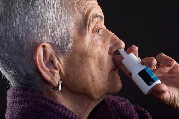 Stara kobieta z sprayem do nosa