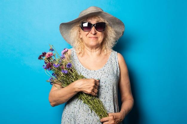 Stara kobieta z uśmiechem w kapeluszu z szerokim rondem i sukienką trzyma bukiet kwiatów na niebieskiej ścianie.
