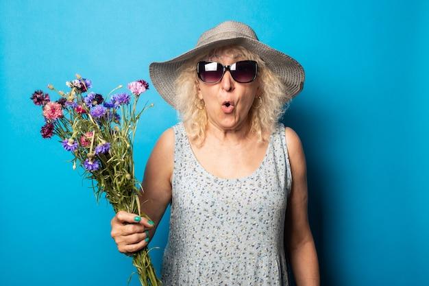 Stara kobieta z zdziwioną twarzą w kapeluszu i sukience z szerokim rondem trzymająca bukiet kwiatów na niebieskiej ścianie.