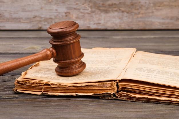 Stara koncepcja książki prawa. otwarta, zniszczona książka z drewnianym młotkiem dworskim.