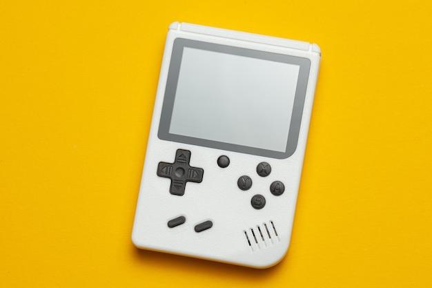 Stara konsola do gier. gamepad jest biały na żółtym tle.