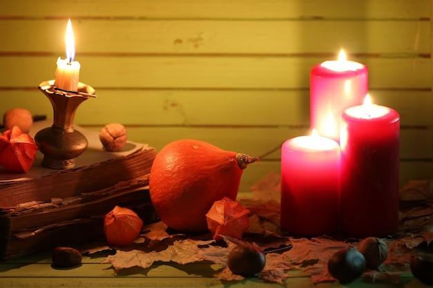 Stara książka dynia i świeca na drewnianym stole