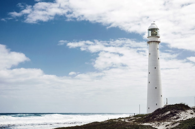 Stara latarnia morska na brzegu pod zachmurzonym niebem w cape town, republika południowej afryki