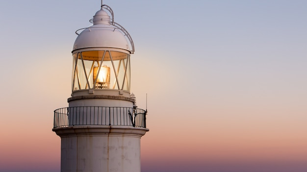 Stara latarnia morska na wybrzeżu z pięknym zachodem słońca w tle
