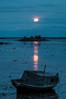 Stara łódź podczas odpływu pod czerwonym księżycem