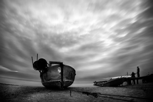 Stara łódź rybacka na plaży morza czarnego po burzy z dramatycznym niebem i poruszającymi się chmurami w czerni i bieli. ludzie są na tylnym molo. słońce za chwilę prześwieci przez chmury. długa ekspozycja.